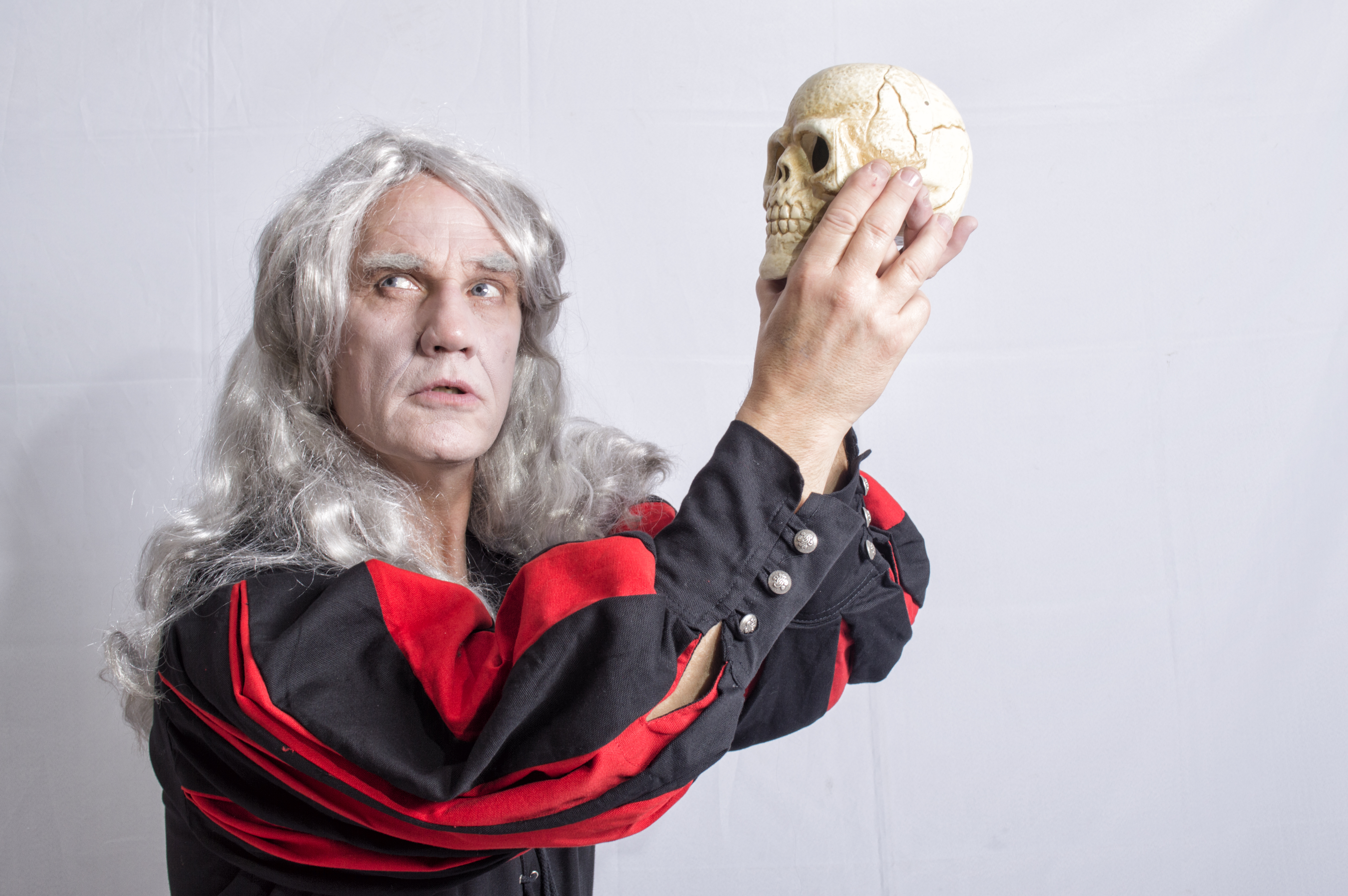Mature man dressed as Hamlet holding a skull