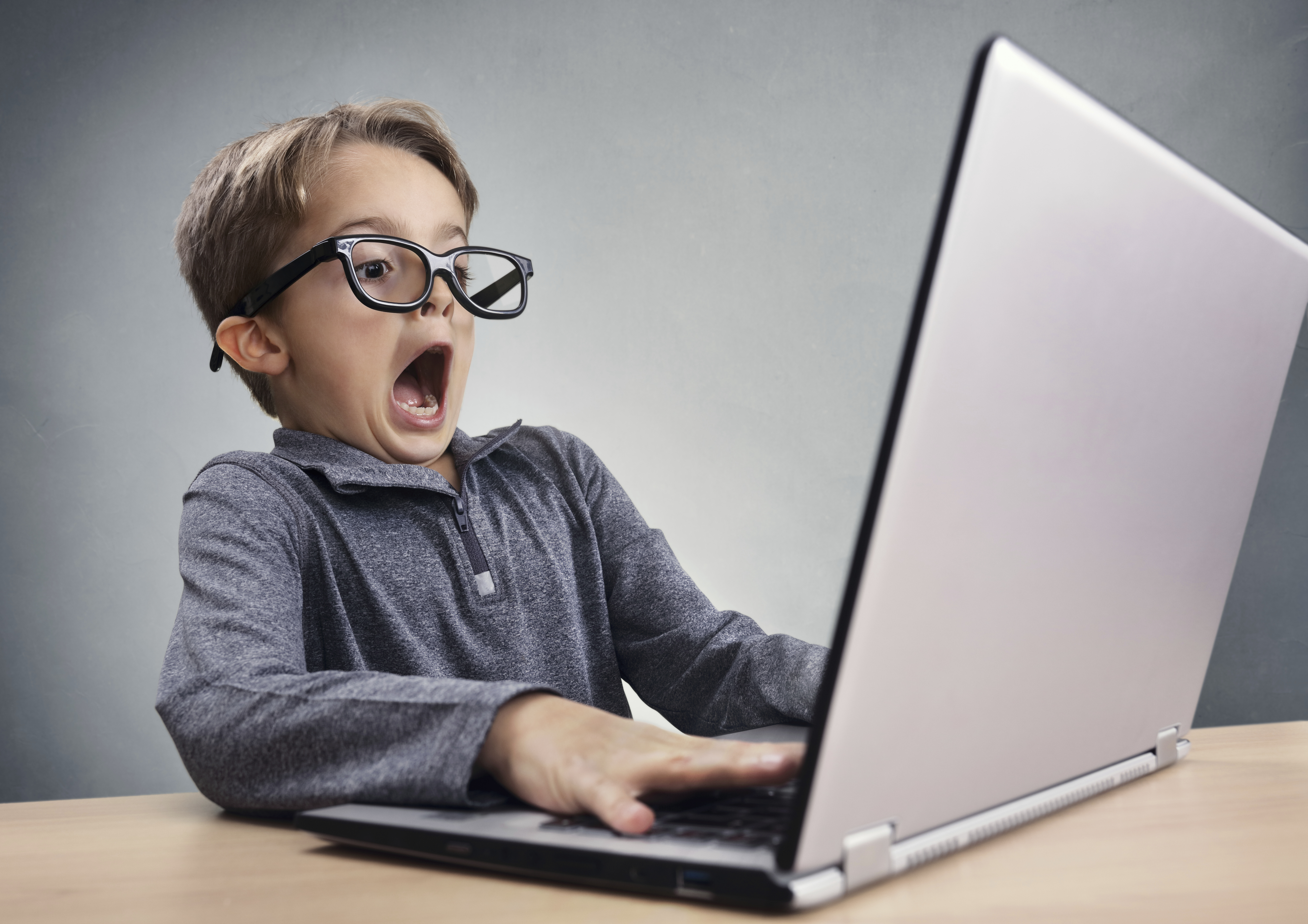 Shocked and surprised boy on the internet with laptop computer